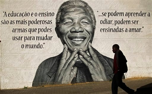"""A man walks past a mural of the former South African President Nelson Mandela that reads in Portuguese: """"Eduction and teaching are the most powerful weapons which you can use to change the world"""", left."""