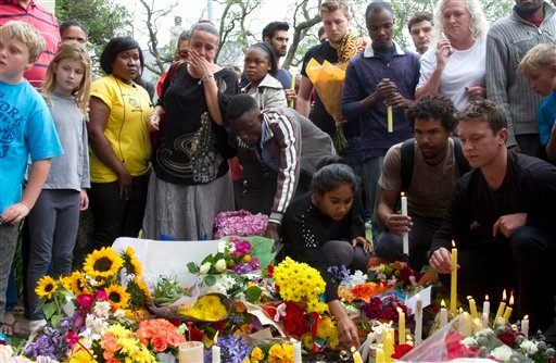 Mourners lay floral and candle tributes to former South African president Nelson Mandela outside his Johannesburg home, Friday, Dec. 6, 2013.
