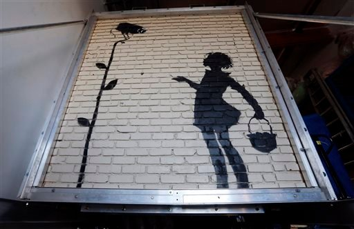"""Flower Girl,"" a delicate stencil on a massive brick wall by popular street artist Banksy, is displayed in a warehouse in the greater Los Angeles area Wednesday, Dec. 4, 2013."