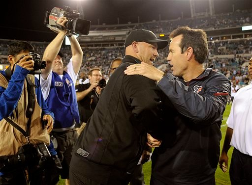 Jacksonville Jaguars head coach Gus Bradley, left, shakes hands with Houston Texans head coach Gary Kubiak, right, after an NFL football game, Thursday, Dec. 5, 2013, in Jacksonville, Fla.