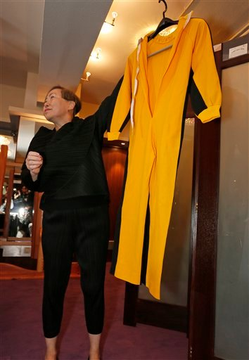 """Anna Lee, vice-chairman of Spink auction house, holds Bruce Lee's original yellow jumpsuit he wore in """"Game of Death"""" during an auction preview in Hong Kong, Monday, Dec. 2, 2013."""