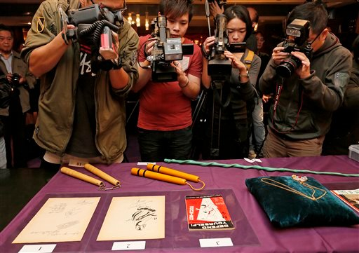 Bruce Lee's most iconic martial arts weapons, including a pair of yellow lacquered wooden nunchaku, second from left, are displayed during an auction preview in Hong Kong, Monday, Dec. 2, 2013.
