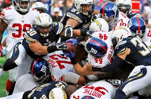 New York Giants running back Peyton Hillis carries the ball into the end zone while San Diego Chargers linebacker Manti Te'o attempts to take the ball away on a 1-yard touchdown run.