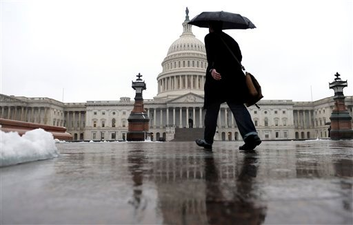 A person walks on Capitol Hill in Washington, Monday, Dec. 9, 2013, as rain, snow, sleet and freezing rain affected most of the U.S. Mid-Atlantic region on Sunday and into Monday. (AP Photo/Susan Walsh)
