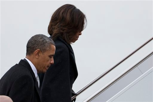 President Barack Obama and first lady Michelle Obama board Air Force One to travel to South Africa for a memorial service in honor of Nelson Mandela on Monday, Dec. 9, 2013 in Andrews Air Force Base, Md. (AP Photo/ Evan Vucci)