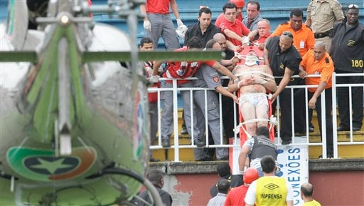 An injured fan is carried on a stretcher after clashes with team fans during a Brazilian league soccer match between Atletico Paranaense and Vasco da Gama in Joinville, southern Brazil, Sunday, Dec. 8, 2013.