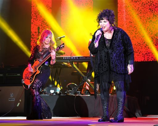 FILE - This June 17, 2013 file photo shows Nancy Wilson, left, and Ann Wilson of Heart performing on opening night of the Heartbreaker Tour at the Cruzan Amphitheater in West Palm Beach, Fla. (AP)