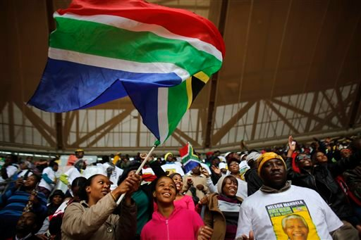 A woman waves a South African national flag ahead of the memorial service for former South African president Nelson Mandela at the FNB Stadium in the Johannesburg, South Africa township of Soweto, Tuesday Dec. 10, 2013. (AP Photo/Markus Schreiber)
