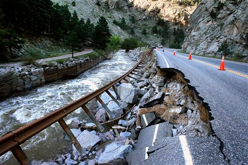 In this Sept. 20, 2013, file photo, a guardrail hangs away from a closed canyon road, which links Boulder with the mountain town of Nederland, and which is washed out in places by recent flooding, up Boulder Canyon, west of Boulder, Colo.