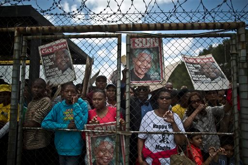 Mourners queue after waiting for hours to get into a bus to go to the Union Buildings where the casket of Former President Nelson Mandela lies in state for three days, in Pretoria, South Africa, Wednesday, Dec. 11, 2013. (AP Photo/Muhammed Muheisen)