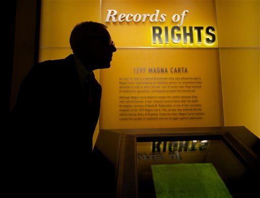 """Philanthropist David Rubenstein talks about the Magna Carta, on display in the glass case, during a press preview of the """"Records of Rights"""" Permanent Exhibition in the new David M. Rubenstein Gallery at the National Archives in Washington. (AP)"""
