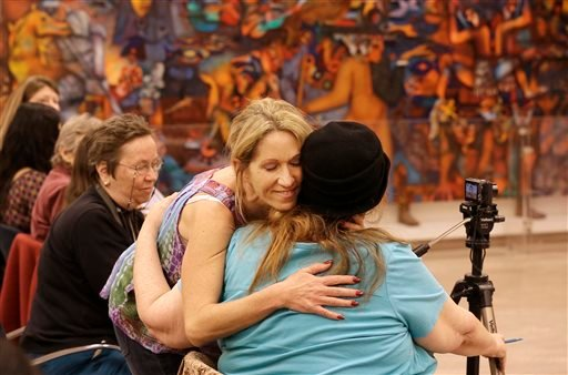 Sex worker Kristen D'Angelo, facing, hugs sex worker activist Carol Leigh at a meeting in San Francisco Nov. 12, 2013. (AP Photo/Jeff Chiu)
