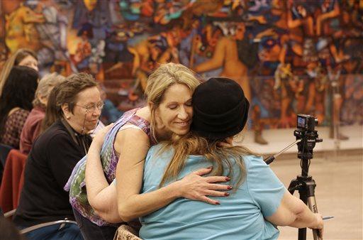 Sex worker Kristen D'Angelo, facing, hugs sex worker activist Carol Leigh at a meeting in San Francisco Nov. 12, 2013. (AP Photo/Jeff Chiu)