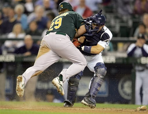 In this Sept. 27, 2006, file photo, Oakland Athletics' Dan Johnson, left, collides with Seattle Mariners' Kenji Johjima at home plate but was out on the play as Johjima held onto the ball in the ninth inning of a baseball game at Safeco Field.