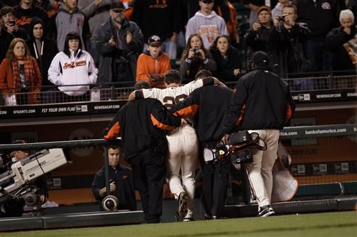 In this May 25, 2011, file photo, San Francisco Giants catcher Buster Posey (28) is helped from the field after a home plate collision with Florida Marlins' Scott Cousins during the 12th inning of a baseball game in San Francisco.