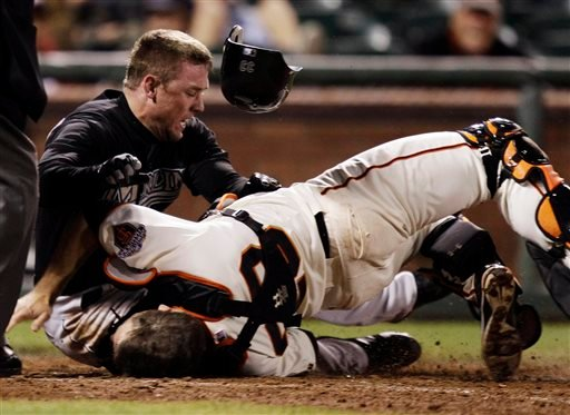 In this May 25, 2011, file photo, Florida Marlins' Scott Cousins, top, collides with San Francisco Giants catcher Buster Posey on a fly ball hit by Marlins' Emilio Bonifacio during the 12th inning of a baseball game in San Francisco.