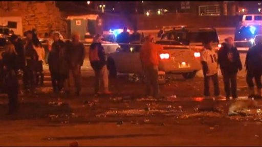 In this image from television provided courtesy of KMGH-THEDENVERCHANNEL.COM people mill around the area where at least three people were stabbed Thursday night Dec. 12, 2013.