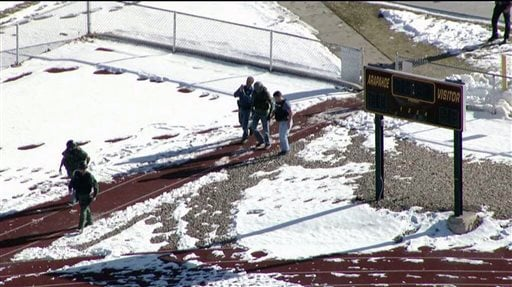 In this still image taken from video provided by Fox 31 Denver, police respond to reports of a shooting at Arapahoe High School in Centennial, Colo. Friday, Dec. 13, 2013.