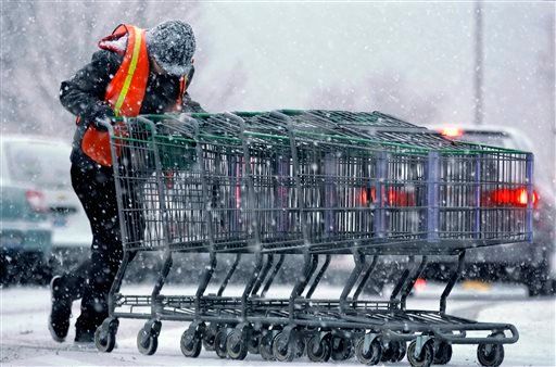 A shopping center employee struggles against strong winds and falling snow as a fast moving winter storm moves into the Midwest Friday, Dec. 13, 2013, in Springfield, Ill. (AP)
