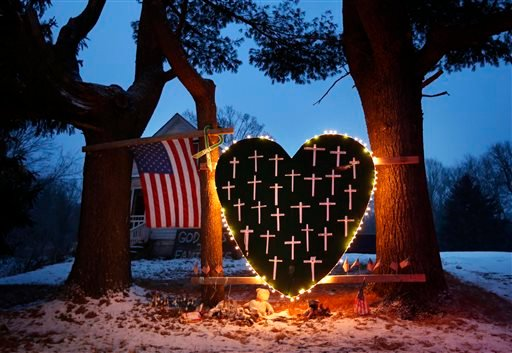 A makeshift memorial with crosses for the victims of the Sandy Hook massacre stands outside a home in Newtown, Conn., Saturday, Dec. 14, 2013, the one-year anniversary of the shootings. (AP Photo/Robert F. Bukaty)