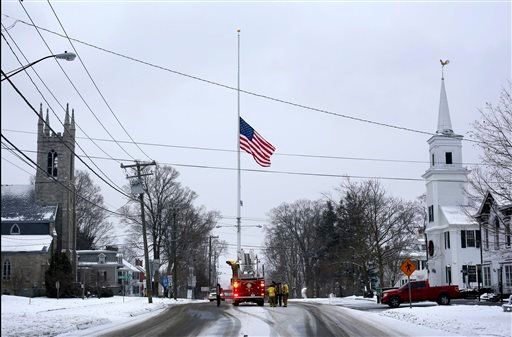 On the first anniversary of the Sandy Hook massacre, firefighters lower the town's flag on Main Street to half-staff in honor of the victims, Saturday, Dec. 14, 2013, in Newtown, Conn. (AP Photo/Robert F. Bukaty)