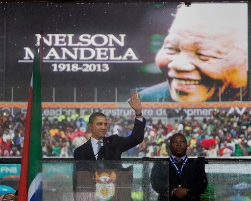 In this Dec. 10, 2013, photo, President Barack Obama waves as he arrives to speak at the memorial service for former South African president Nelson Mandela at the FNB Stadium in the Johannesburg, South Africa township of Soweto.