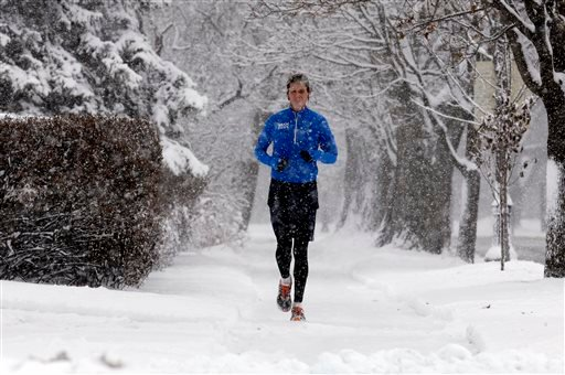 A jogger runs on a snowy sidewalk in Evanston, Ill. on Saturday, Dec. 14, 2013. Snow continued to fall over the Chicago area into northwest Indiana. (AP Photo/Nam Y. Huh)