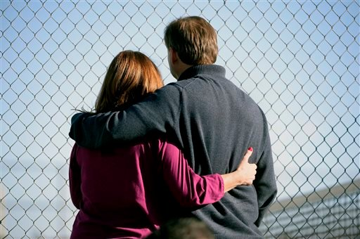 Parents stand along the tennis court fence hoping to see if their child is standing outside on the football field after a gunman was spotted inside Arapahoe High School on Friday, Dec. 13, 2013, in Centennial, Colo.