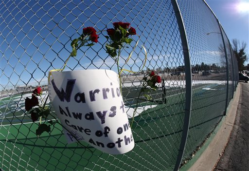 Roses and a sign of support are woven into a cyclone fence around a tennis court at Arapahoe High School in Centennial, Colo., on Saturday, Dec. 14, 2013.