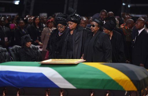 Winnie Madikizela-Mandela, left, Nelson Mandela's former wife, left and Nelson Mandela's widow Graca Machel stand over the former South African president's casket during his funeral service in Qunu, South Africa, Sunday, December 15, 2013.