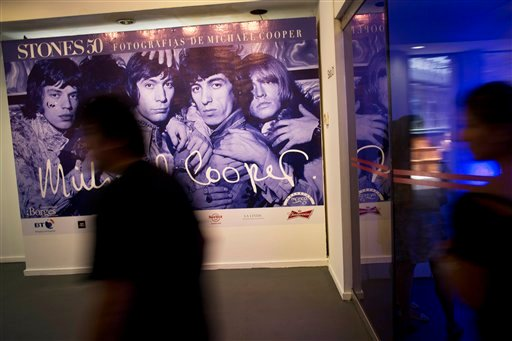 A man walks past a banner featuring a Michael Cooper photo of the Rolling Stones, on the eve of the inauguration of Stones 50, an exhibit of Cooper's photos.