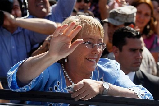 Presidential candidate and former President Michelle Bachelet waves to supporters after casting her vote during presidential elections in Santiago, Chile, Sunday, Dec. 15, 2013.