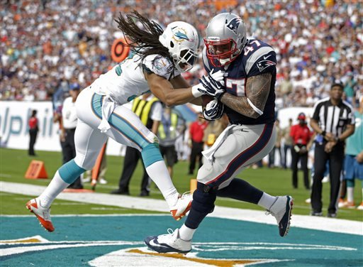New England Patriots tight end Michael Hoomanawanui (47) grabs a touchdown pass as Miami Dolphins outside linebacker Philip Wheeler (52) defends during the first half of an NFL football game on Sunday, Dec. 15, 2013, in Miami Gardens, Fla.