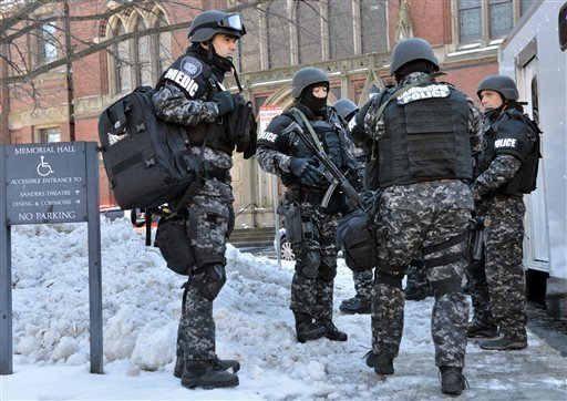 Tactical police assemble outside a building at Harvard University in Cambridge, Mass., Monday, Dec. 16, 2013.