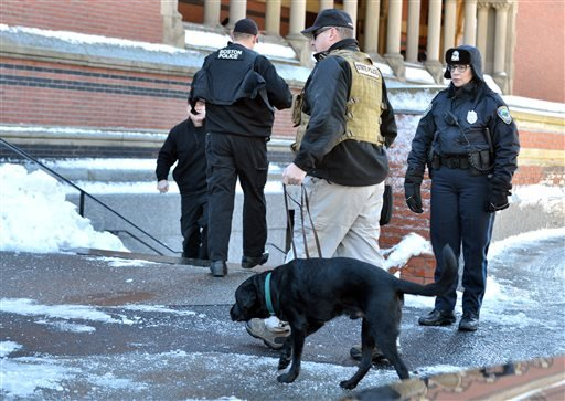 A police officer leads a dog into a building at Harvard University in Cambridge, Mass., Monday, Dec. 16, 2013.