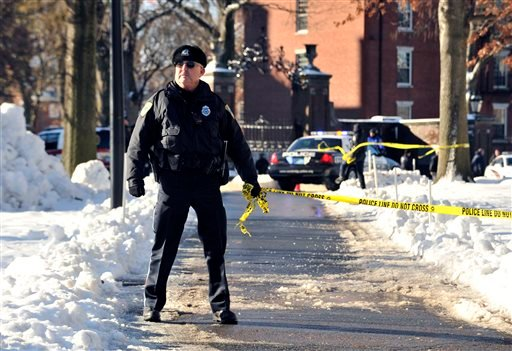 A police officer holds tape to keep people out from an area at Harvard University in Cambridge, Mass., Monday, Dec. 16, 2013.