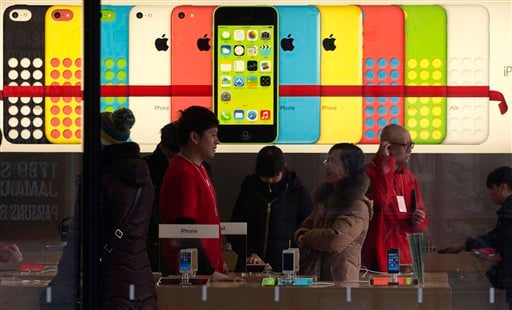 A woman talks to a salesperson in front of an advertisement for iPhones at Apple's retail store in Beijing Monday, Dec. 16, 2013.