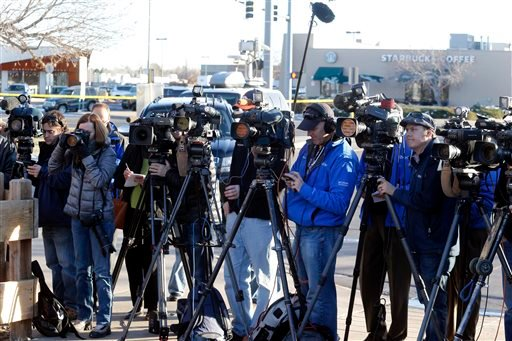 Media cover a briefing by Arapahoe County Sheriff Grayson Robinson Saturday, Dec. 14, 2013, at Arapahoe High School in Centennial, Colo.