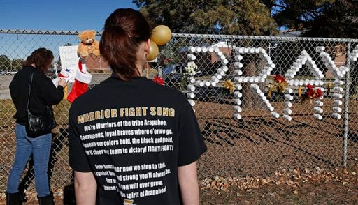 Arapahoe High School junior Emily Evans, right, waits while her mother Cristina writes a note to leave at a makeshift memorial bearing the name of wounded student Claire Davis. (AP)