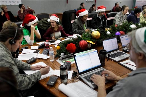 FILE - In this Dec. 24, 2012 file photo, Lizzie Solano, center, and her sister Sarah take phone calls from children during the annual NORAD Tracks Santa Operation, in Colorado Springs, Colo. (AP)