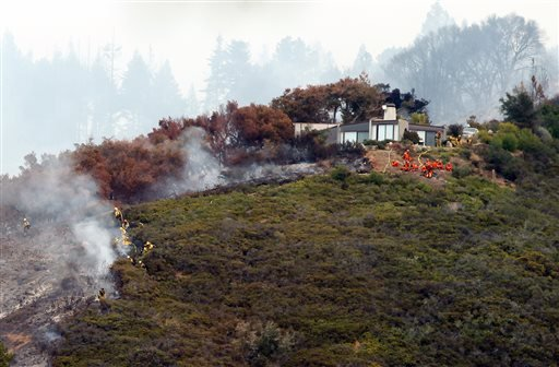 Fire crews work to contain the fire atop Pfeiffer Ridge, Monday, Dec. 16, 2013, in Big Sur, Calif.