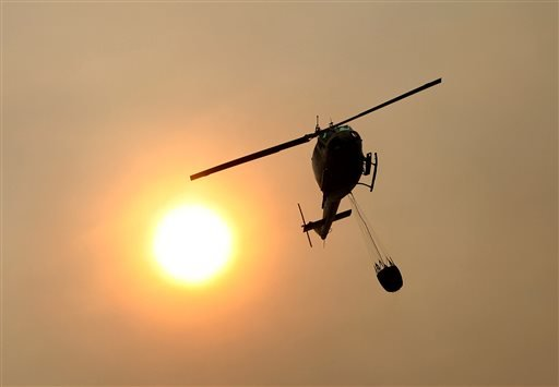 A Cal Fire helicopter flies over Pfeiffer Ridge on Monday, Dec. 16, 2013, in Big Sur, Calif.
