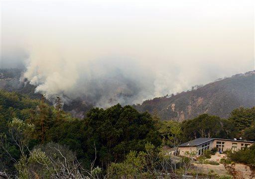Smoke rises above Pfeiffer Ridge, Monday, Dec. 16, 2013, in Big Sur, Calif.