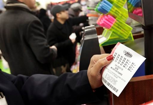 A woman plays the Mega Millions lottery at a shop in New York's Penn Station, Tuesday, Dec. 17, 2013.