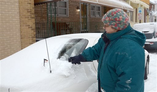 Rita Lanum of Hazleton, Pa., uses a brush to clear snow off her car parked along East Maple Street, Hazleton on Tuesday, Dec. 17, 2013 after a few inches of snow fell early in the morning. (AP Photo/Hazleton Standard-Speaker, Eric Conover)