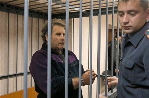 In this Thursday, Sept. 26, 2013 file photo a police officer guards the US captain of the Greenpeace ship 'Arctic Sunrise', Peter Willcox in a cage in a court room in Murmansk, Russia. (AP Photo/Efrem Lukatsky, File)