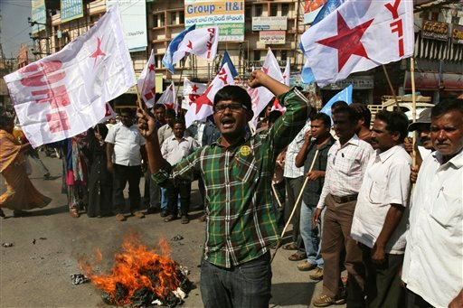 Left party activists shout slogans after burning an effigy of the U.S. to protest against the alleged mistreatment of New York based Indian diplomat Devyani Khobragade, in Hyderabad, India Dec. 18, 2013. (AP Photo/Mahesh Kumar A.)