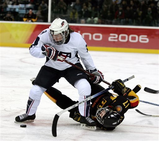 In this Feb. 12, 2006, file photo, the United States' Caitlin Cahow (8) upends Germany's Sara Seiler during the first period of a 2006 Winter Olympics ice hockey match in Turin, Italy.