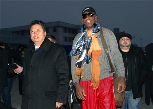 Former NBA basketball star Dennis Rodman walks with Vice Minister of North Korea's Sports Ministry, Son Kwang Ho, as Rodman arrives at the international airport in Pyongyang, North Korea on Thursday, Dec. 19, 2013.