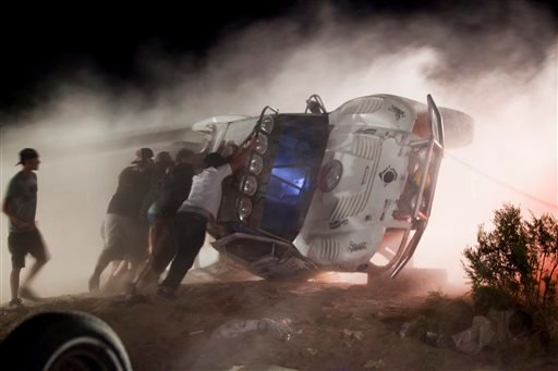 In this Aug. 15, 2010 file photo, people push an overturned off-road race truck upright after it went out of control and ran into a crowd of spectators during a race in Lucerne Valley, Calif.